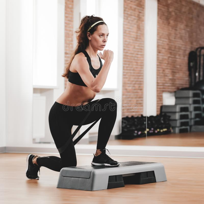 Sportswoman training with stepper. Portrait of strong fit woman training with stepper in modern fitness club royalty free stock images