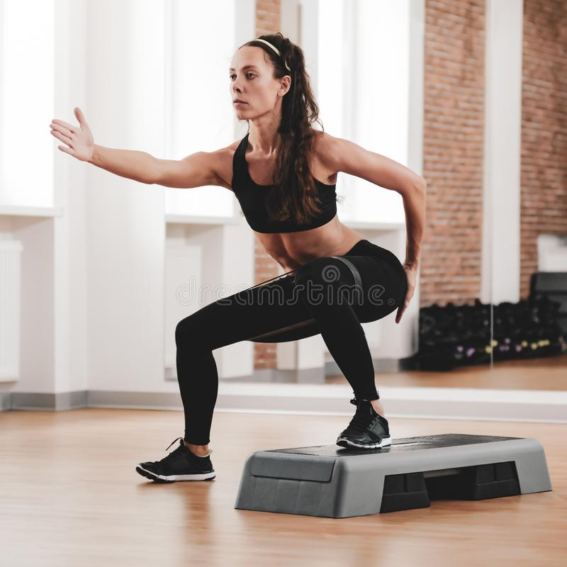 Sportswoman training with stepper. Portrait of strong fit woman training with stepper in modern fitness club stock photography