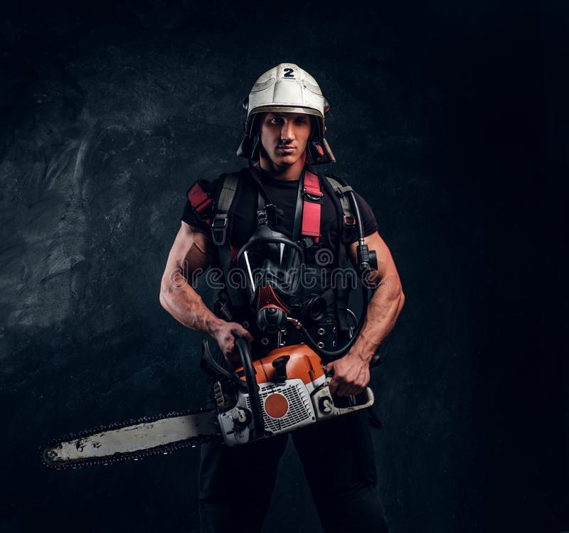 Portrait of strong man with chainsaw and oxygen mask. Attractive young handyman in helmet is looking forward. He holds chainsaw in hands. Man has oxygen mask on royalty free stock image