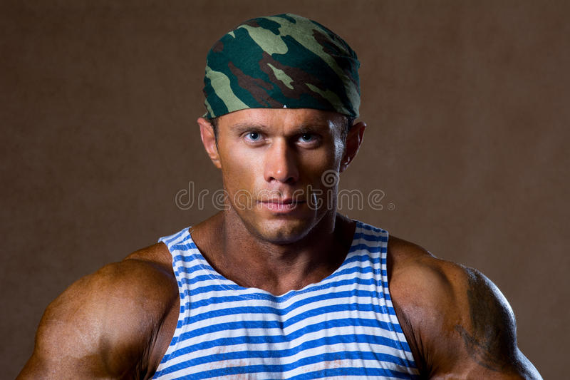 Portrait of a strong muscular man in a striped shirt. Special Forces royalty free stock image