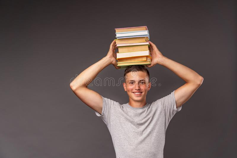 Portrait of a student boy with a backpack and a stack of books in his hands on his head. funny positive high school teenager. back royalty free stock photo
