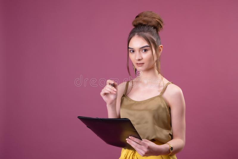 Portrait of student girl with pen and paper folder. Young pretty worker writing something in her papers stock photography