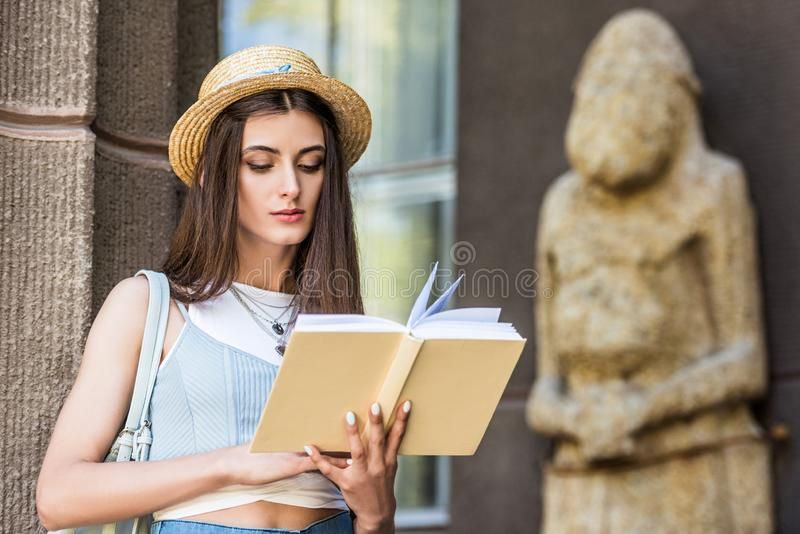 portrait of student in straw hat reading book royalty free stock photography