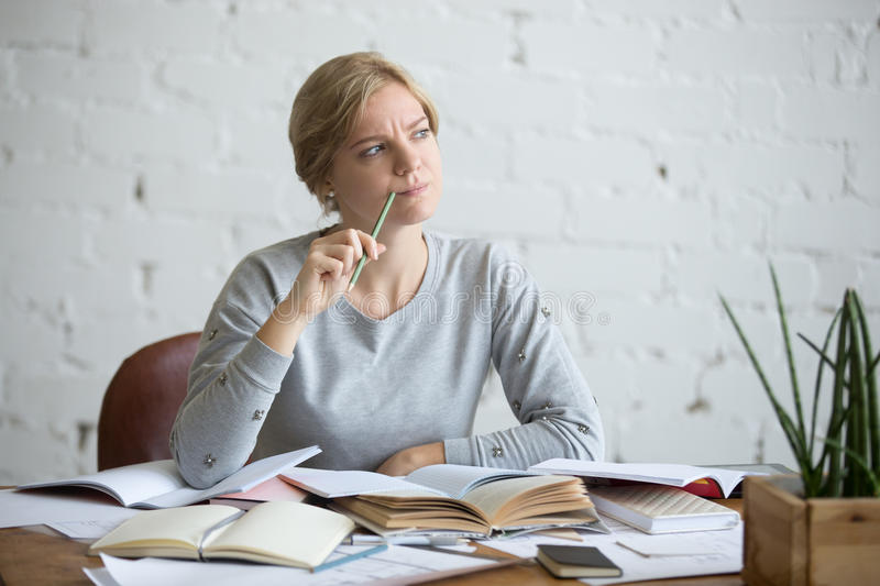 Portrait of a student woman at the desk, frowned. Portrait of a student woman sitting at the desk, frowned, looking aside lifestyle. Education concept photo royalty free stock images