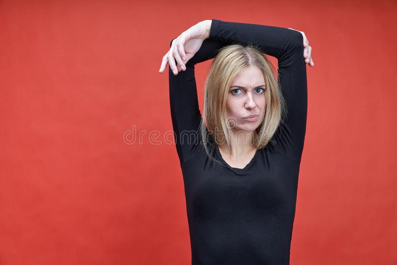 Portrait in Studio on red background young skinny light-skinned women hands up over his head with an irritable expression stock image