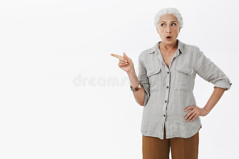 Portrait of stunned intense and questioned grandmother with gray hair in casual outfit looking and pointing left with stock photo