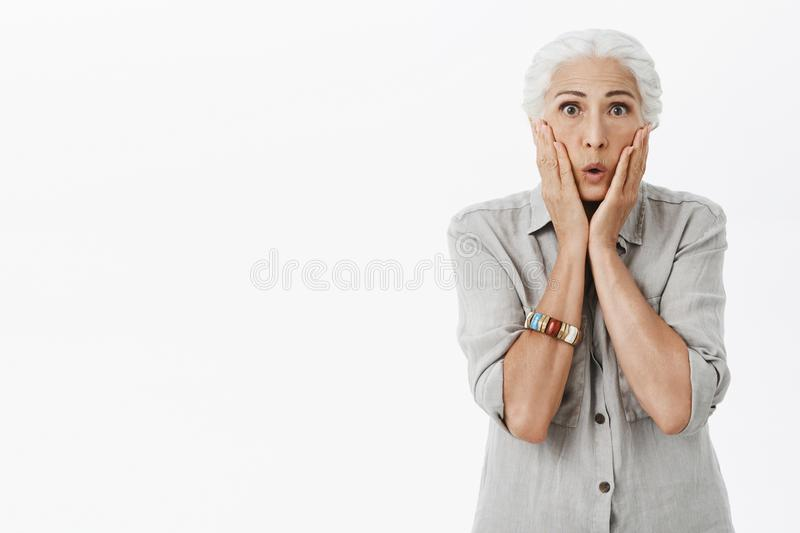 Portrait of stunned and shocked worried old lady with white hair folding lips and touching cheeks from shock and stupor stock photography