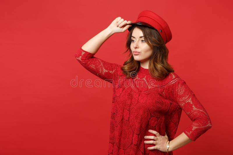 Portrait of stunning confident young woman in lace dress holding cap and looking aside isolated on bright red wall stock image