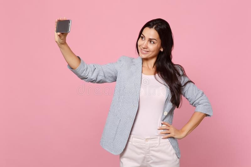 Portrait of stunning pretty young woman in striped jacket doing selfie shot on mobile phone isolated on pink pastel royalty free stock photo