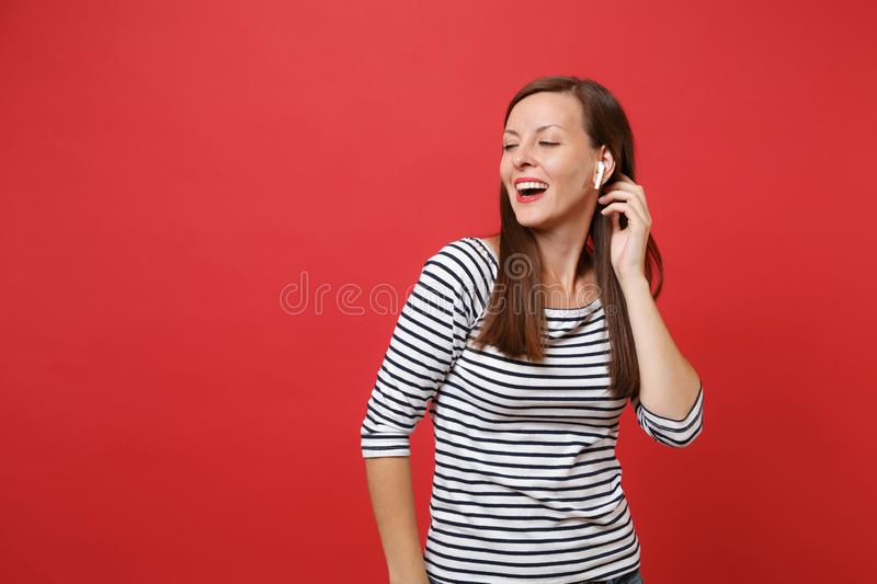Portrait of stunning young girl in casual striped clothes with wireless earphones listening music isolated on bright red. Wall background. People sincere royalty free stock photos