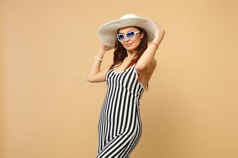 Portrait of stunning young woman in black and white striped dress, hat and sunglasses looking camera  on pastel royalty free stock images