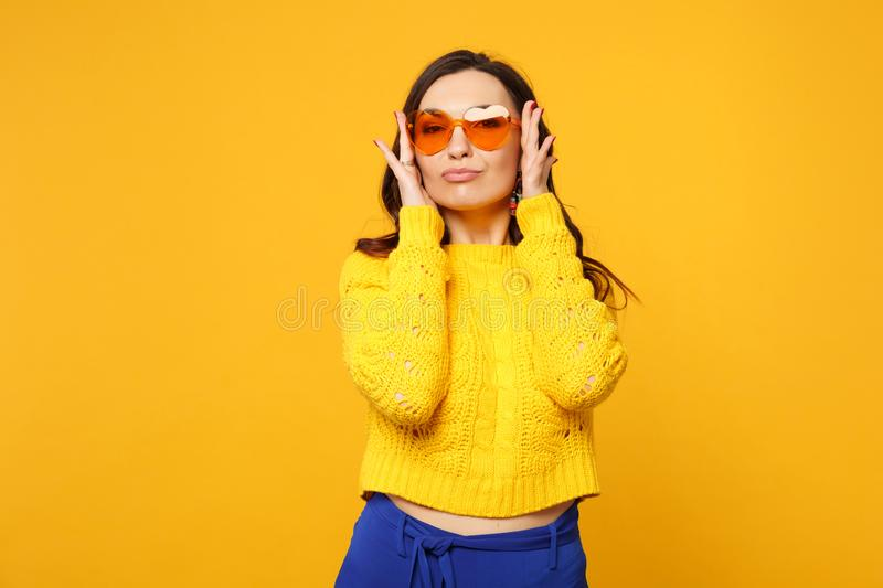 Portrait of stunning young woman in sweater, blue trousers, heart glasses keeping hands near face  on yellow stock photography