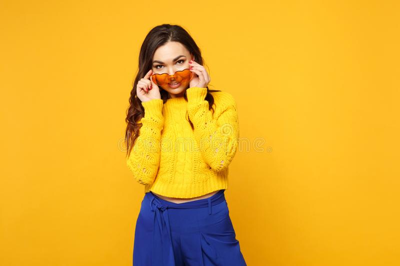 Portrait of stunning young woman in sweater, blue trousers holding heart glasses, looking camera isolated on yellow stock photography