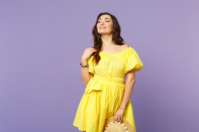 Portrait of stunning young woman in yellow dress holding summer hat looking aside isolated on pastel violet wall. Background in studio. People sincere emotions royalty free stock images