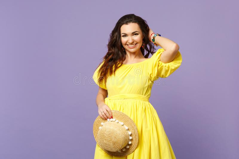 Portrait of stunning young woman in yellow dress holding summer hat putting hand on head  on pastel violet. Background in studio. People sincere emotions stock photos