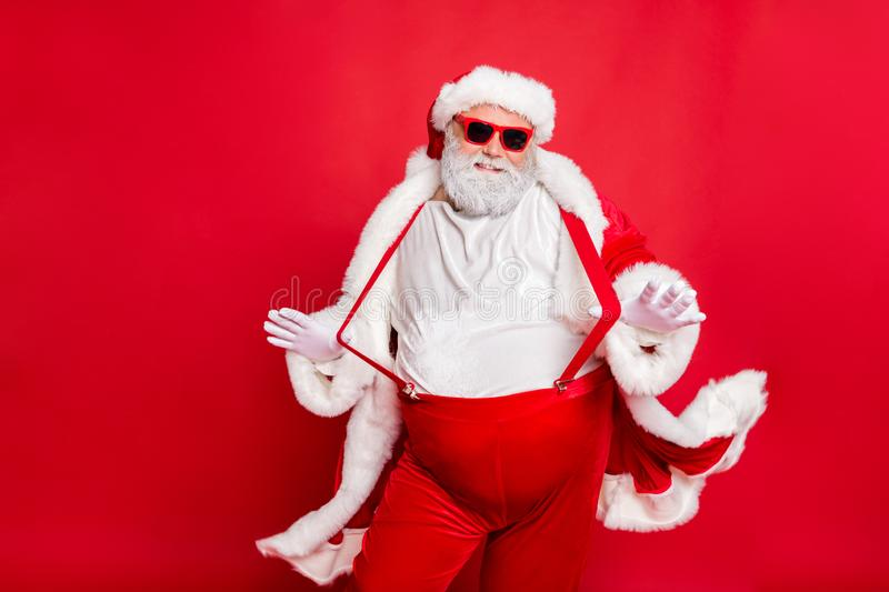 Portrait of style fat overweight santa claus with big funny belly abdomen touch his suspenders overalls posing like a. Portrait of style fat overweight santa stock photo