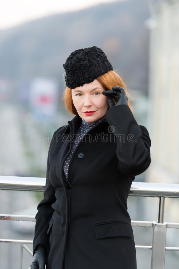 Portrait of styled woman in black coat. Red hair lady in coat, hat and gloves. Woman`s serious look at you. royalty free stock photos