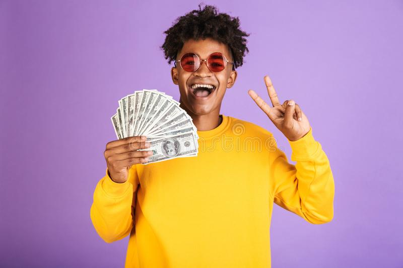 Portrait of stylish african american man wearing sunglasses smiling while holding dollars money banknotes, isolated over violet b. Portrait of stylish african stock images