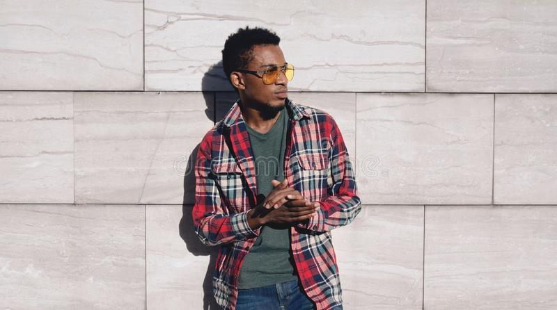 Portrait stylish african man wearing red plaid shirt, looking away, guy posing on city street, gray brick wall. Background royalty free stock photos