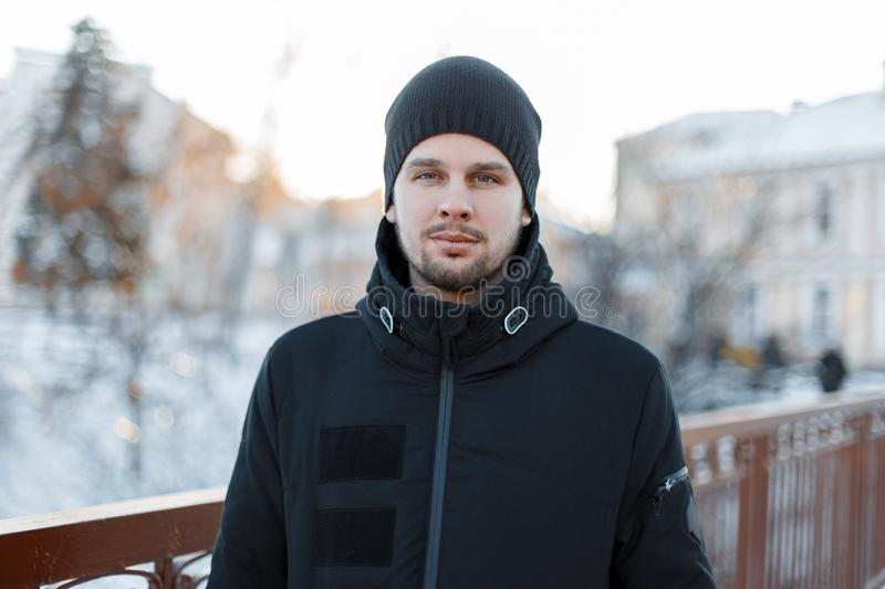 Portrait of a stylish attractive young man with a beard in a stylish winter black jacket in a knitted hat on a warm winter day. Brutal fashionable guy royalty free stock photography