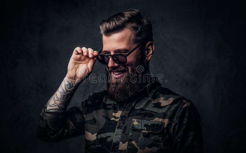 Portrait of a stylish bearded guy with tattooed hands in the military shirt holding hand on sunglasses and laughs stock photo