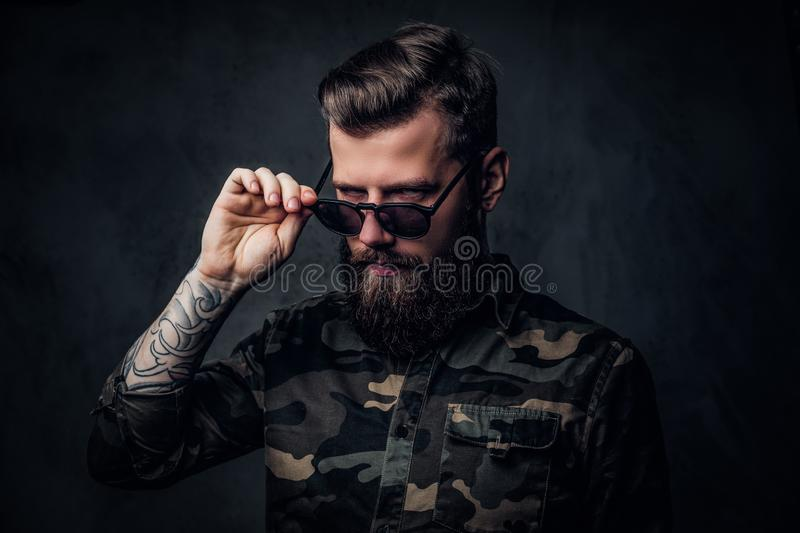 Portrait of a stylish bearded guy with tattooed hands in the military shirt holding hand on sunglasses and looking at a stock photo