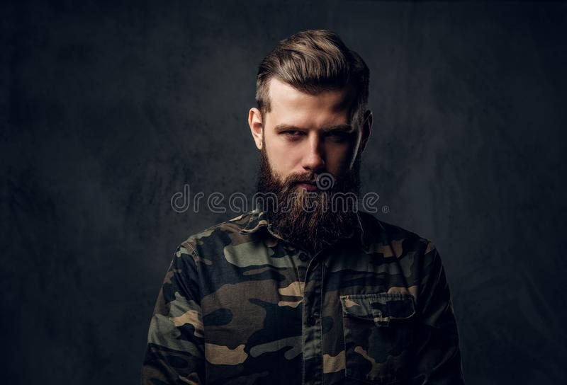 Portrait of a stylish bearded guy with tattooed hands in the military shirt. Studio photo against dark wall stock image