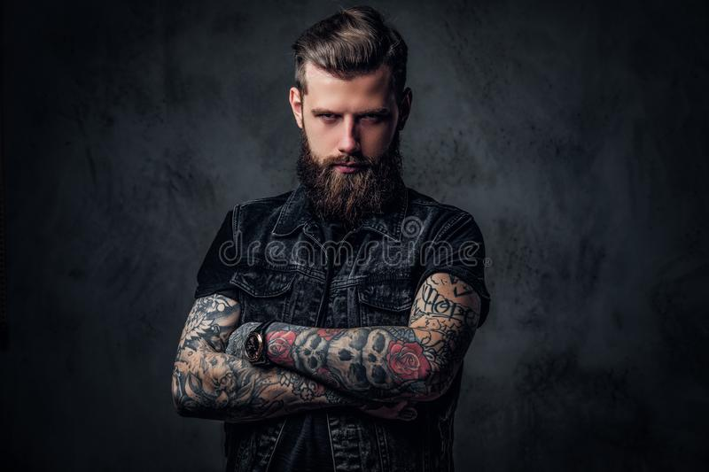 Portrait of a stylish bearded guy with tattooed hands. Studio photo against dark wall royalty free stock image