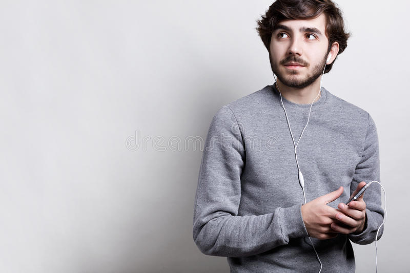 Portrait of stylish bearded man dressed in grey casual sweater listening to the music or audiobook with his earphones and smartpho royalty free stock images