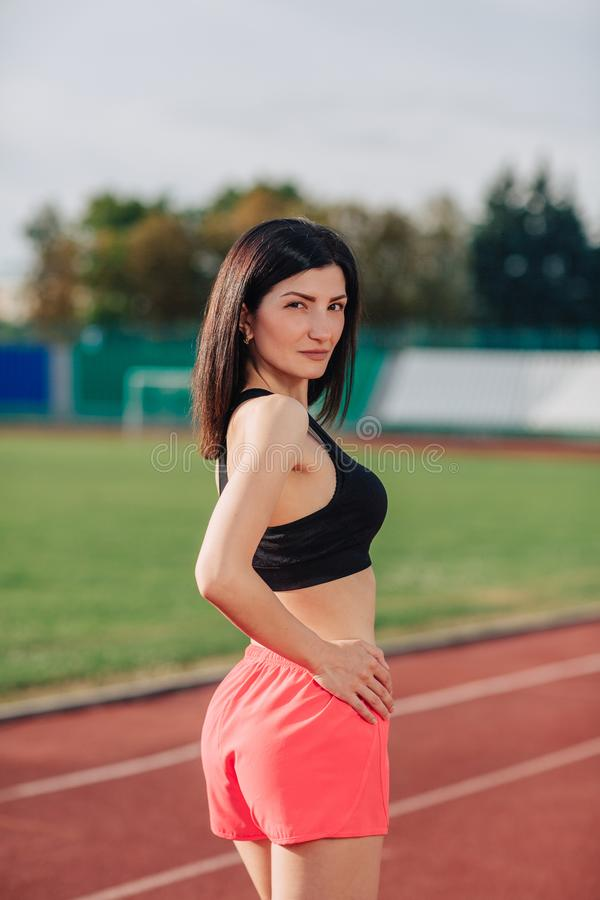 Portrait of stylish beautiful brunette woman with a perfect figure in pink shorts and top posing for the camera on running track. At the stadium stock photos