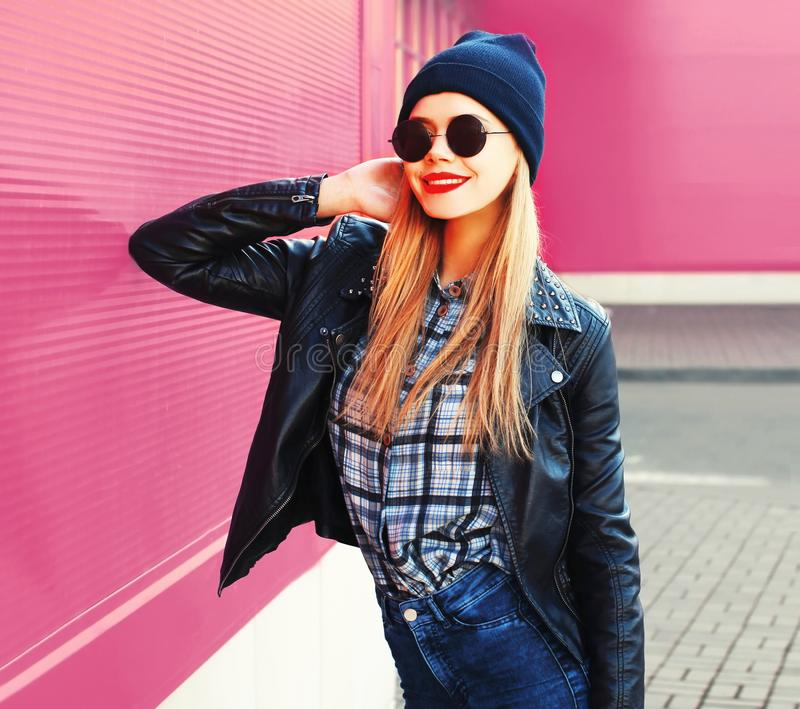portrait stylish blonde smiling woman in rock black style jacket, hat posing on city street royalty free stock photography