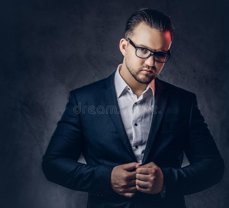 Portrait of a stylish businessman with serious face in an elegant formal suit and glasses. royalty free stock photo