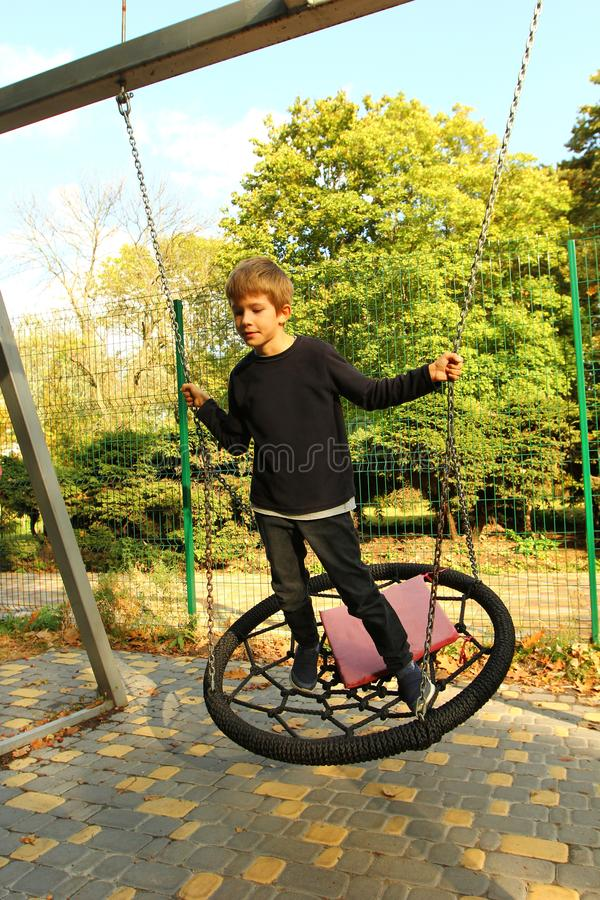 Portrait of a stylish caucasian boy standing on a weaved round swing in the autumn park stock photos