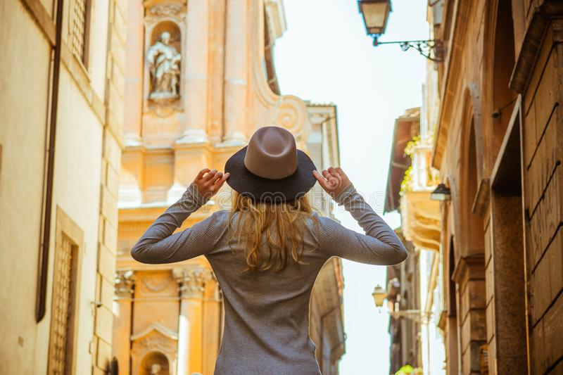 Back view of woman wearing greu sweater. Nice hat, hands up. Beautiful architecture. stock image