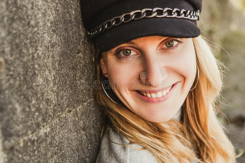 Close up shot of stylish young woman smiling adainst the wall. Beautiful female model. Blonde middle-aged woman. stock image