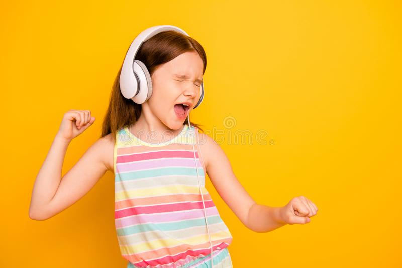 Portrait of stylish crazy kid dancing hearing melody her playlist isolated over yellow background. Portrait of stylish crazy kid dancing, hearing melody her royalty free stock image