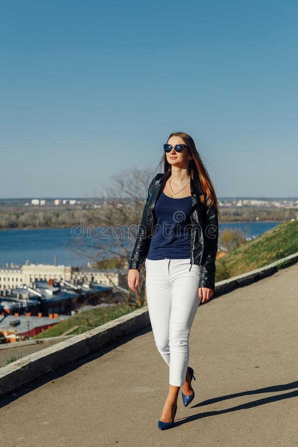 Portrait of a stylish dark-haired girl in sunglasses, she is in a leather jacket stock photo