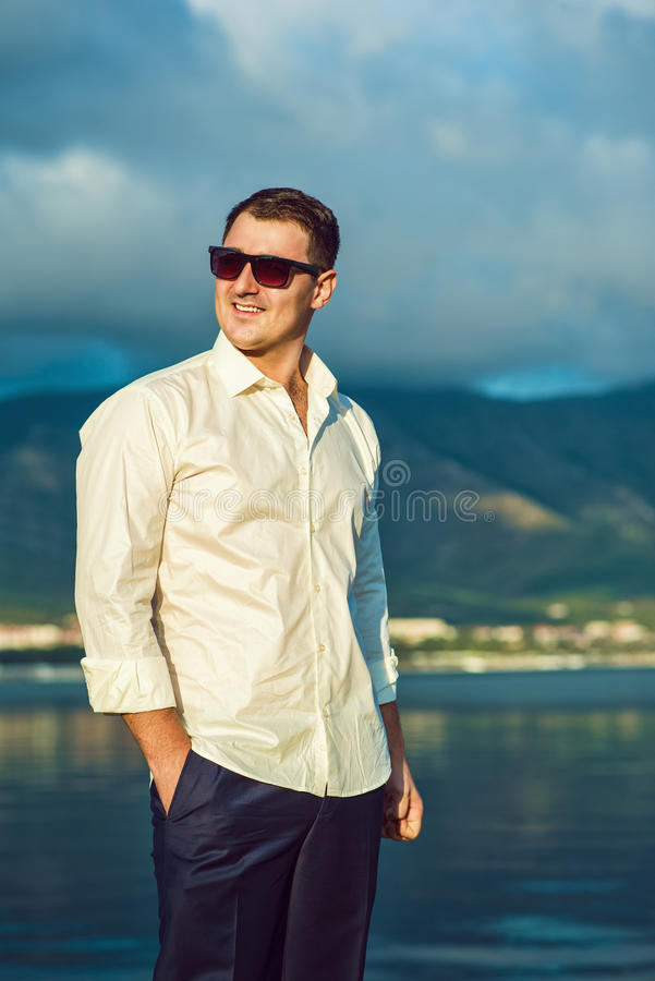Portrait of stylish dark-haired young man in sunglasses at the seaside royalty free stock photography