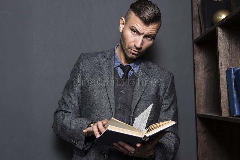 Portrait of stylish, elegant young man in suit with book. Young handsome man reads book. stock photo