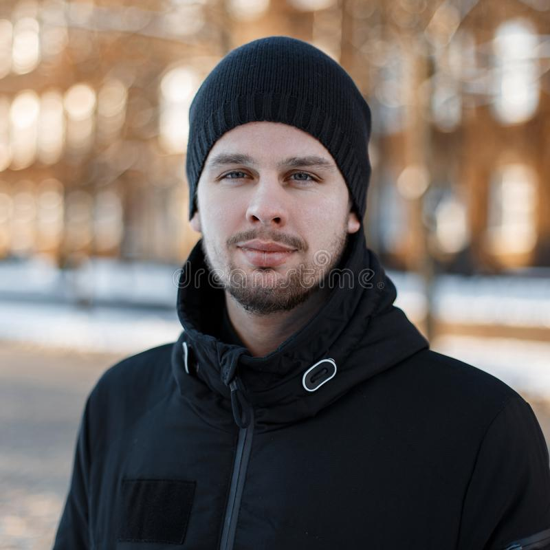 Portrait of a stylish friendly handsome young man with a beard in a fashionable winter black jacket in a black knitted hat. On the background of vintage modern stock image