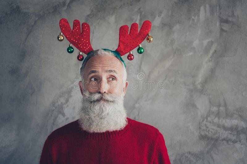 Portrait of stylish funky old man in reindeer headband enjoy christmas party x-mas celebration wear red modern sweater. Portrait of stylish funky old man in stock images