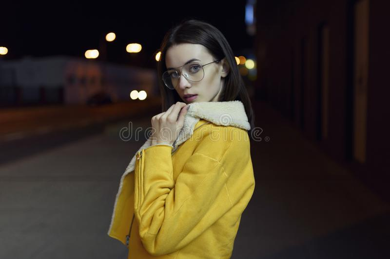 Stylish girl posing in yellow jacket and glasses, lit by city centre lights by night. Womenswear fashion. Bokeh background stock images