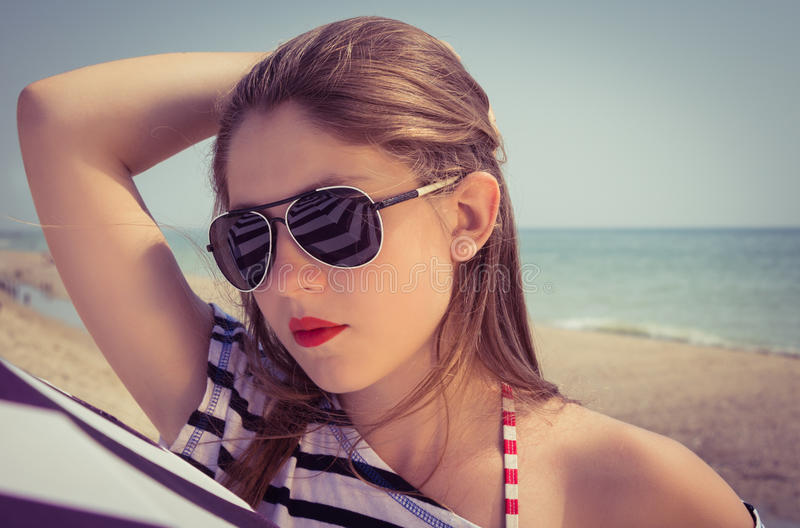 Portrait of a stylish girl in a striped t-shirt and sunglasses b stock photo