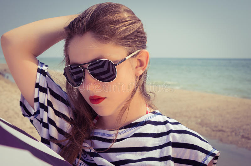 Portrait of a stylish girl in a striped t-shirt and sunglasses royalty free stock image