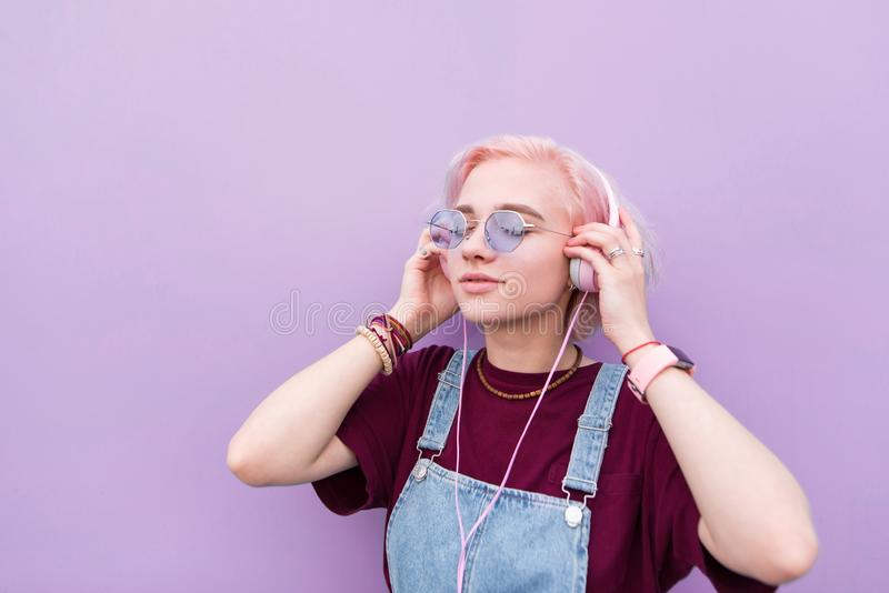 Portrait of a stylish girl who listens to music in pink headphones on the background of a purple wall stock photos