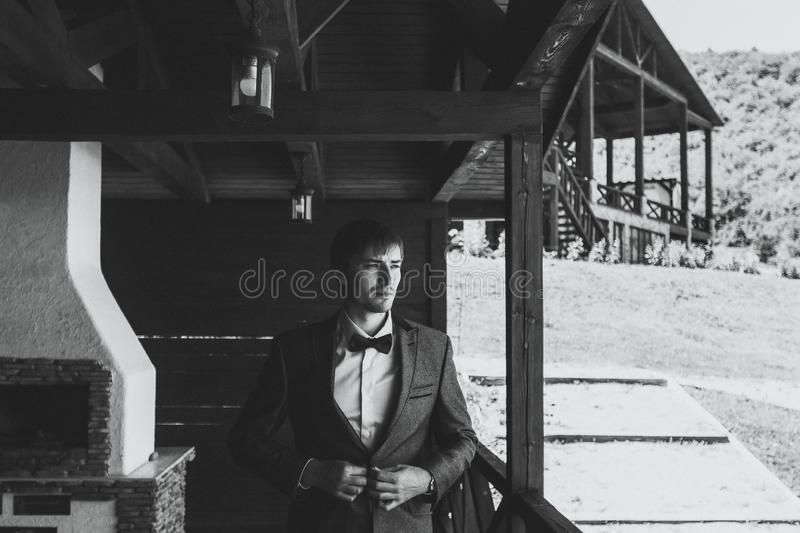 Portrait of stylish groom in a suit and bow-tie on outdoor wooden terrace. Of manor stock photography