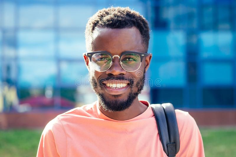 Portrait stylish and handsome African student American man in glasses smiling toothy professor on the street stock image