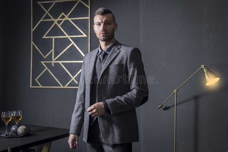 Portrait of stylish handsome business man in luxury apartment. Businessman in dark interior. man in fashionable business royalty free stock photography