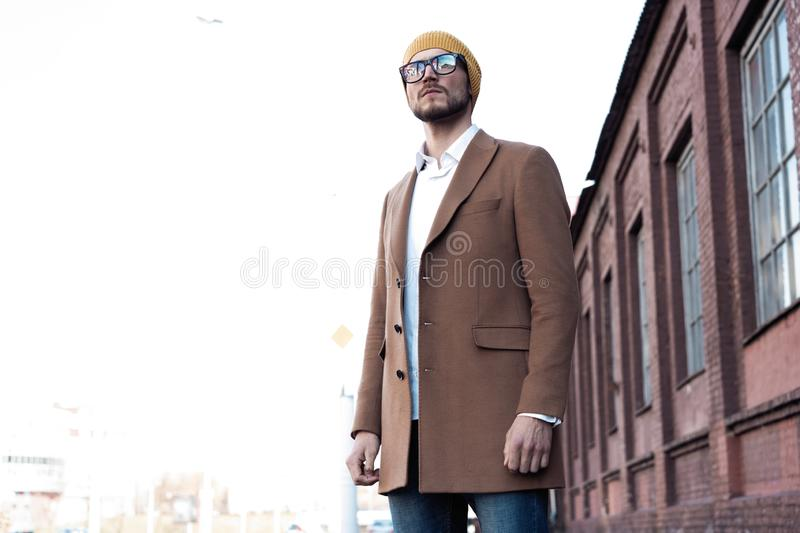 Portrait of stylish handsome young man in glasses with bristle standing outdoors. Man wearing jacket and shirt. stock photography