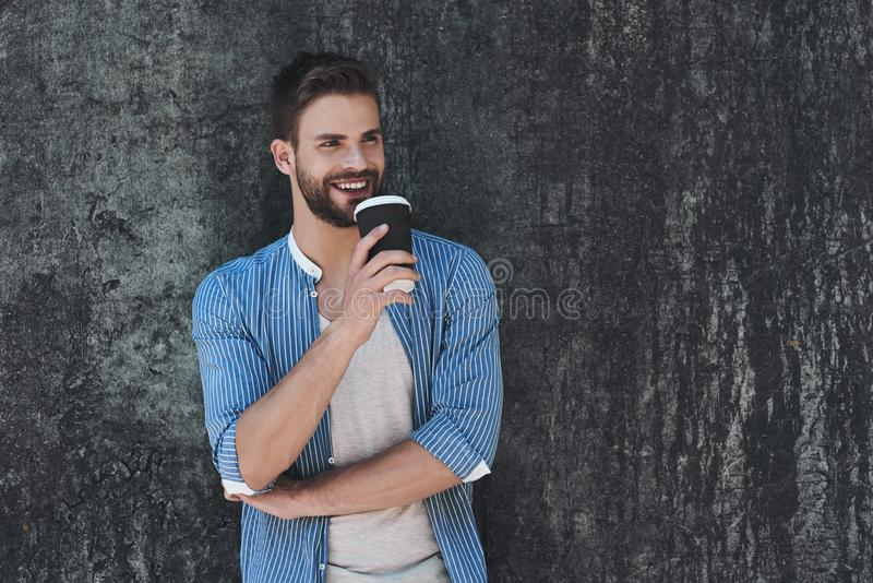 Portrait of stylish handsome young man standing outdoors and leaning on wall with cofee stock images
